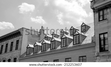 Several dormers on a roof in black and white - stock photo