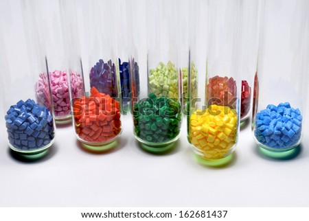 several dyed polymer resins in test glasses in laboratory - stock photo