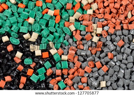 several dyed polymer resins ready for color separating by special equipment machines - stock photo