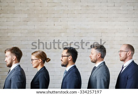 Several employees standing in queue along wall - stock photo