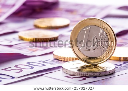 Several 500 euro banknotes and coins are adjacent. Symbolic photo for wealt.Euro coin balancing on stack with background of banknotes. - stock photo
