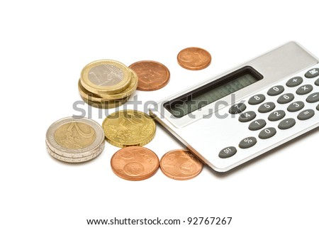 Several euro coins and calculator on white background - stock photo
