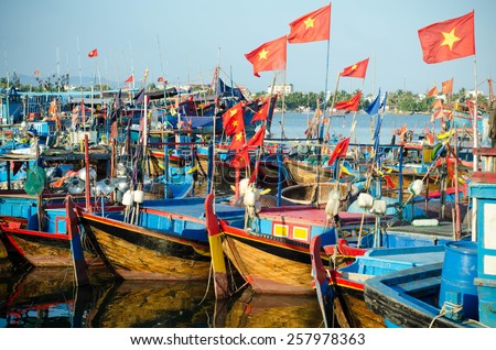 several Fishing boats with red flags in marina at Nha Trang, Vietnam - stock photo