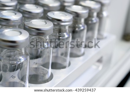 Several glass vials. Laboratory equipment for dispensing fluid samples. Shallow depth of field. - stock photo