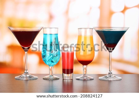 Several glasses of different drinks on bright background - stock photo