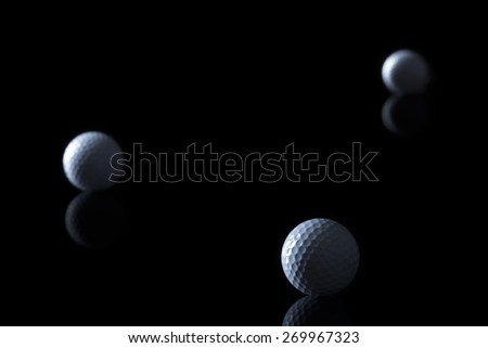 Several golf balls isolated on black background with blank copy space for text. - stock photo
