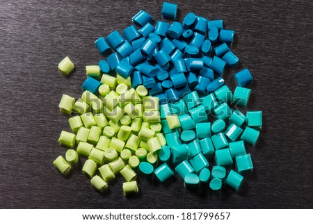 several green dyed polymer resins on metal surface - stock photo