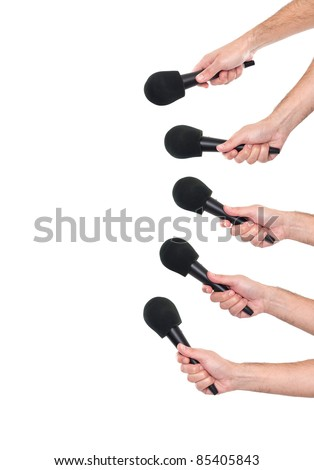 Several hands holding microphones - stock photo