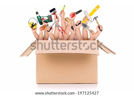 Several hands inside a cardboard box with construction tools - stock photo