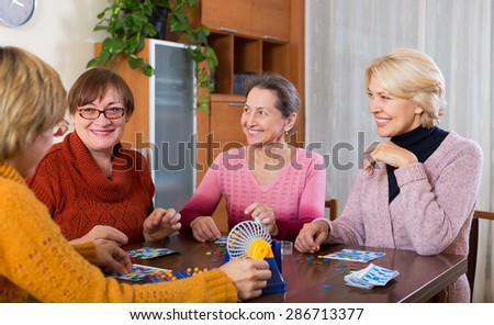 Several happy female pensioners playing board game at the room in home - stock photo