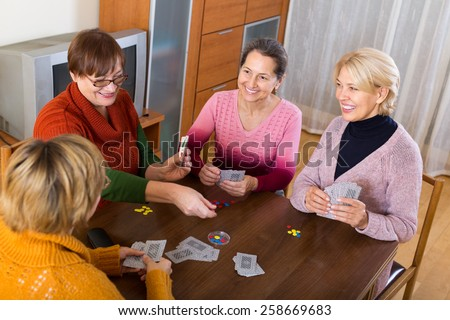 Several happy female pensioners playing cards at home - stock photo