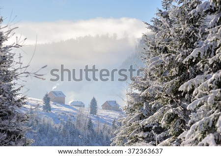 Several houses are situated on a hillside covered with snow. Blue sky, cloud and mist mountains there in the background. Smoke coming from the chimney. Winter sunny, cold day in the mountains. - stock photo