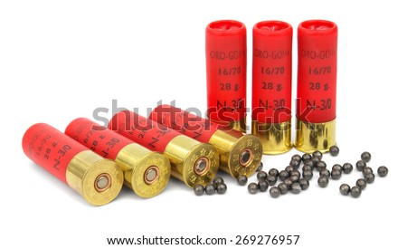 Several hunting cartridges and scattered pellets of cartridges isolated on a white background. - stock photo