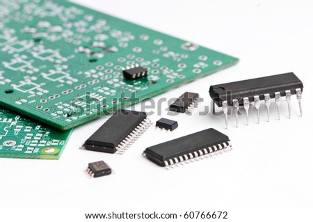 several integrated microelectronics components and green microcircuit board - stock photo