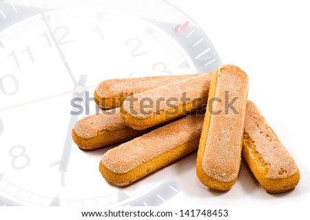 several ladyfinger biscuits on clock's background - stock photo