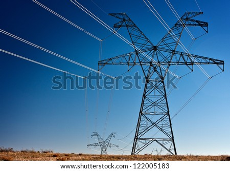 Several large high voltage power transmission towers silhouetted - stock photo