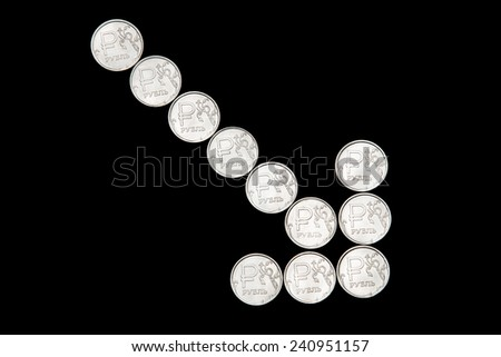 Several metal Russian ruble coins on black background form down arrow - stock photo