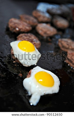 Several mini Kobe beef burgers cooking on a grill.  Two are topped with a fresh fried quail egg. - stock photo