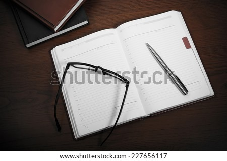 Several notebooks lie on brown wooden table - stock photo