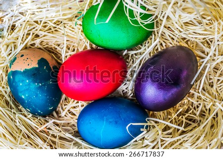 Several painted Easter eggs laid in straw nest - stock photo