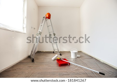 Several painting tools paint roller, ladder, tray, paint, foil, hardhat  prepared for painting of a room. - stock photo