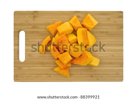 Several pieces of cut butternut squash on a wood cutting board. - stock photo
