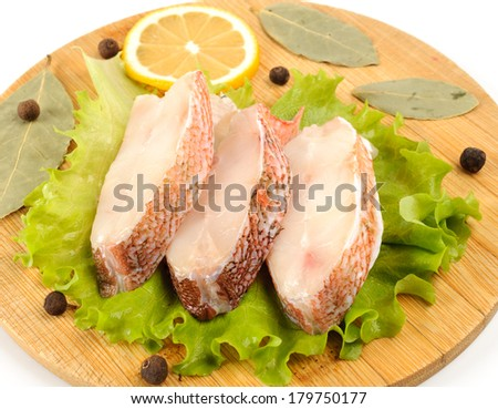 Several pieces of sea bass on a cutting board. - stock photo