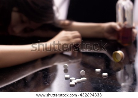 Several pill spilled on table Near bottle of alcohol. - stock photo