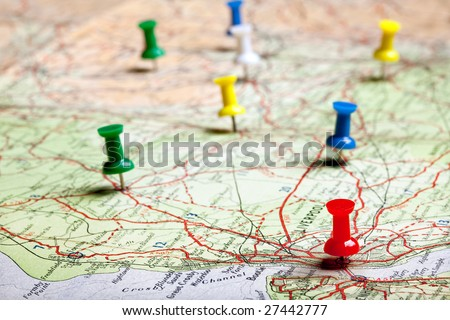 Several pushpins on a road-map of a tourist - stock photo