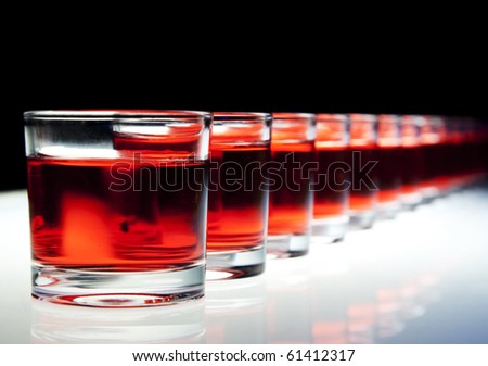 Several red alcohol shots on a bar. - stock photo