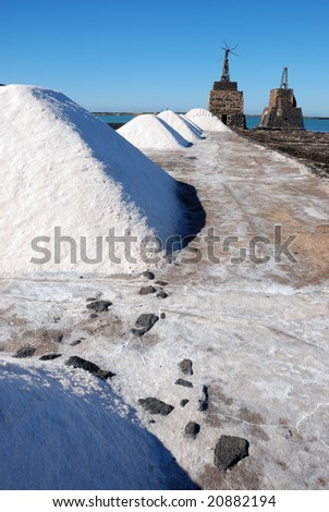 Several salt mountains with two old windmills at the back - stock photo