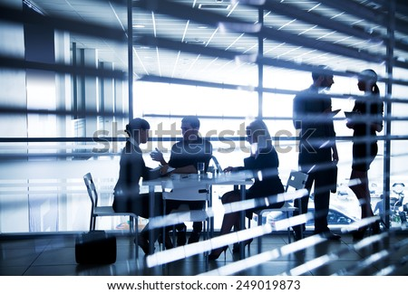 Several silhouettes of businesspeople interacting  in office - stock photo