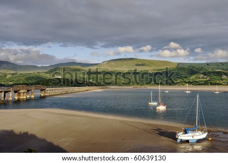 Several small boats, with Barmouth Bridge and the Mawddach Estuary - stock photo