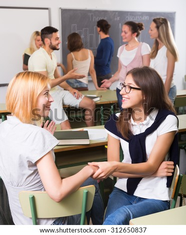 Several smiling students communication sitting in the classroom - stock photo