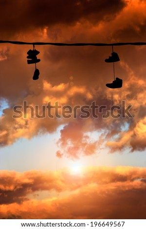 Several sneakers hung at sunset - stock photo