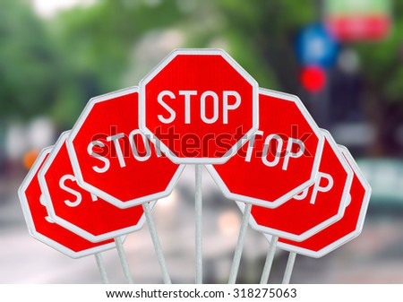 Several STOP sign on blurred city road - stock photo