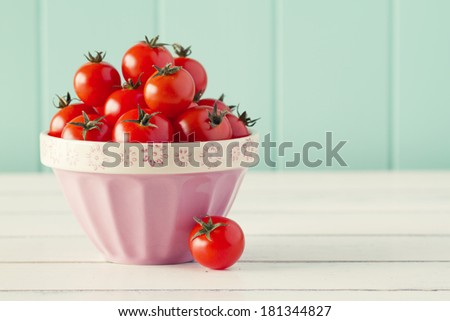 Several tomatoes in a pink bowl on a white wooden table with a robin egg blue background. Retro look. - stock photo