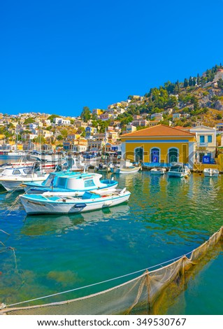 several traditional old fishing boats docked in the main port of Symi island in Greece - stock photo