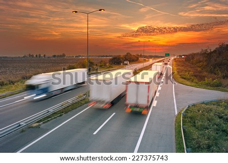 Several trucks in motion blur on the highway at sunset, near Belgrade - Serbia - stock photo