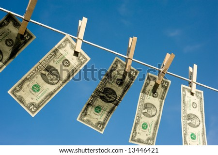 Several two dollar bills on a clothesline in front of a blue sky - stock photo