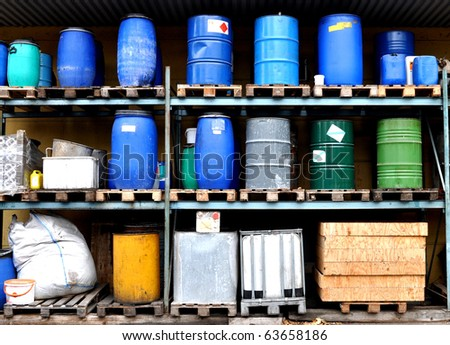 Several types of drums and barrels in a warehouse - stock photo