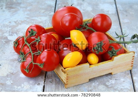 several varieties of tomatoes in a box on the table - stock photo