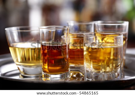 Several various sized shot glasses filled with different whiskeys shot on silver tray in bar setting, space for copy - stock photo
