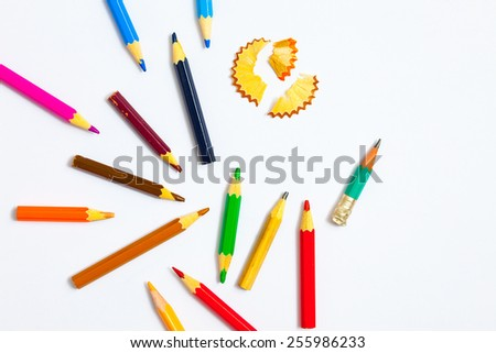 several vintage colored pencils and shavings on white background with copy space, close up - stock photo