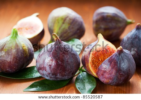 Several whole figs and one halved fig - stock photo