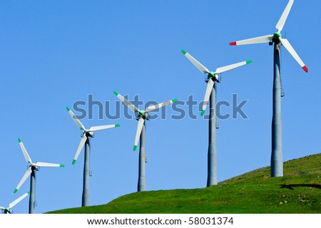 Several wind turbines with green and red blades - stock photo