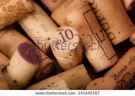 Several Wine Corks on a white background. You can read the Origin of the Wine and or the Vintage on them. - stock photo