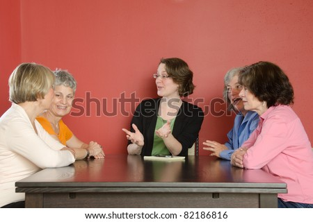 Several women sit around a table in animated conversation with a group leader who might be an instructor or facilitator - stock photo