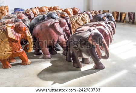 Several wooden elephants standing in a room - stock photo