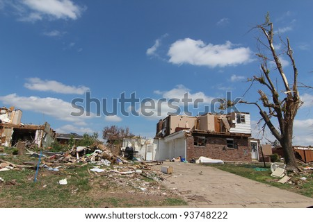 Severe tornado damage is very apparent in the light of a beautiful blue sky sunny day. - stock photo